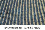 Small photo of Roof tiles texture of a low house ruined and untrained for years