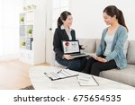 Small photo of friendly confident business woman presenting company marketing record report for young lady and explaining insurance importance in future.