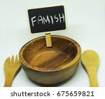 Small photo of Empty wooden bowl attach with blackboard written the word famish on it. Wooden spoon and fork set beside it. Everything on isolated white background.