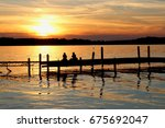 Summer sunset over the lake. Landscape with golden sunset and silhouettes of people enjoying the beautiful evening on a lake Mendota pier in the city of Madison, Wisconsin, USA.