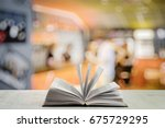 open book on white table in a... | Shutterstock . vector #675729295