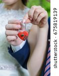 Small photo of Couple holding red wedding lock with cipher closeup