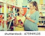 female with girl choosing fresh ... | Shutterstock . vector #675949135