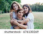 mother and daughters embrace in ... | Shutterstock . vector #676130269