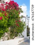 Small photo of Typical Greek house with red flowers on the street in Adamas town. Milos. Cyclades islands. Greece.