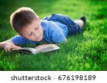 boy reading book  lying down on ... | Shutterstock . vector #676198189