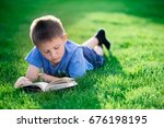 boy reading book  lying down on ... | Shutterstock . vector #676198195