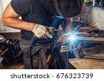 a strong man is a welder in a... | Shutterstock . vector #676323739