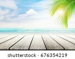 empty wooden table and palm... | Shutterstock . vector #676354219