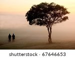 Two People Walking Past A Tree...