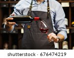 male sommelier pouring red wine ... | Shutterstock . vector #676474219
