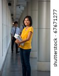 Portrait of a cute laughing college student in yellow t-shirt holding books on a modern university campus. Young female Asian Thai model late teens, early 20s of Chinese descent looking at camera - stock photo