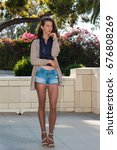 Small photo of Pretty brunette in tan pantyhose, short denim and open toe heels thinking and dreaming in courtyard.