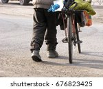 Small photo of Homeless man cross the street with bike.
