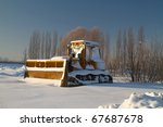 Bulldozer in snowy winter scenery - stock photo