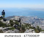 Small photo of Man admiring the wonderful views from Table Mountain over Cape Town and the Atlantic Ocean