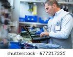 manual worker using a laptop in ... | Shutterstock . vector #677217235