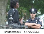a white cop talks to a black... | Shutterstock . vector #677229661