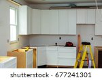 Stock photo custom kitchen cabinets in various stages of installation base for island in center installation of 677241301