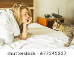 Stock photo girl and cat on the bed 677245327