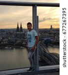 Small photo of attractive young man traveler looking at sunset over the city Cologne from the tower Cologne Panorama, Köln Triangle July 2017 Germany