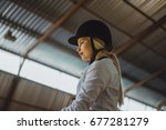 Small photo of A beautiful blonde girl in outfit trains a horse in an arena. Horse riding, horse racing, jumping.