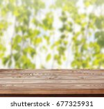 wood table top on abstract blur ... | Shutterstock . vector #677325931