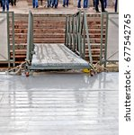 Small photo of Wooden gangway between coast and floating mooring. On embankment blur legs of the people expecting flight or going on the ship. Background.