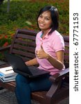 A cute college student wearing pink shirt using a black laptop on lap on outdoor bench gives a thumb up with a smile.  20s female Asian Thai model of Chinese descent looking at camera - stock photo