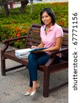 A cute smiling college student wearing pink shirt outside on a university campus bench writing notes into her notepad.  20s female Asian Thai model of Chinese descent looking at camera - stock photo