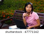 A cute pensive Asian college student wearing pink shirt thinking with laptop on lap sitting outside on a university campus bench. 20s female Asian Thai model of Chinese descent looking away - stock photo
