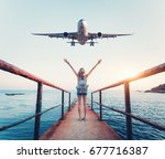Small photo of Airplane and woman at sunset. Summer landscape with girl standing on the sea pier with raised up arms and flying passenger airplane. Woman and landing commercial plane in the evening. Lifestyle