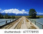 Small photo of Wooden bridge over a river in Kurai. Beautiful Altaic landscape with snow-capped mountains, sky and clouds. River crossing to the mountains.