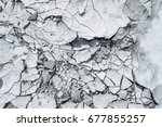 Cracked concrete texture background. Grey surface with cracks close up. A lot of pieces of splintered plaster. Abstract concept of split, dissent, disagreement, discord. Sunny day with shadows. - stock photo