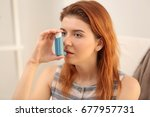 young woman using inhaler for... | Shutterstock . vector #677957731