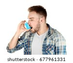 Young Man Using Inhaler For...
