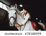 Stock photo a beautiful blonde girl in outfit trains a horse in an arena horse riding horse racing jumping 678188599