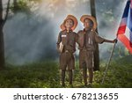 Small photo of Two scouts are reading a book Scout Promise and Law in the woods.