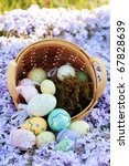 Easter eggs spilling from a basket into a bed of spring flowers. Selective focus on center portion of image where eggs are spilling out with extreme shallow DOF. Some blur on lower portion. - stock photo