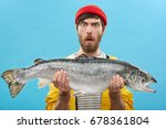 Stock photo headshot of funny emotional young bearded caucasian fisherman in hat and raincoat holding large 678361804