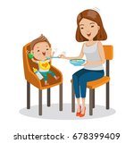 mather is feeding little son.... | Shutterstock .eps vector #678399409