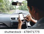 man looking at phone inside car | Shutterstock . vector #678471775