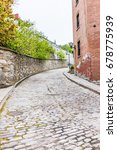 Small photo of Quebec City, Canada - May 30, 2017: Lower old town narrow street with cobblestone road on incline uphill and residential brick house and entrance