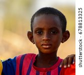 Small photo of FERLO DESERT, SENEGAL - APR 25, 2017: Unidentified Fulani little boy in striped shirt looks ahead. Fulanis (Peul) are the largest tribe in West African savannahs