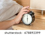 Small photo of Man extend hand reaching to turn off alarm clock switch