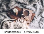 cup of coffee and candle on... | Shutterstock . vector #679027681
