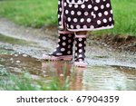 Child's feet playing in a mud puddle. Selective focus on little girl with extreme shallow DOF. Some blur on lower portion. - stock photo
