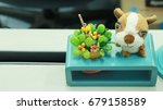Small photo of Green flower and aminal doll on blue small table