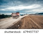 Industrial dumper trucks working on highway construction site, loading and unloading gravel and earth. heavy duty machinery activity - stock photo