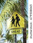 Small photo of Walking ahead under palm trees - road sign